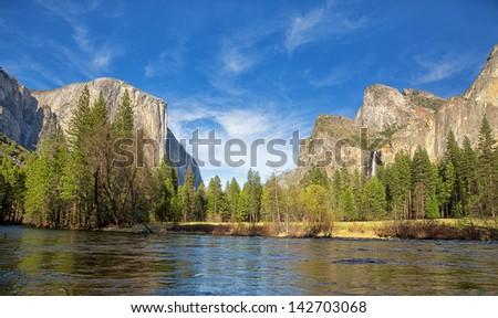 Yosemite Valley panorama showing the El Capitan, the Cathedral Rocks and the Bridalveil Falls,  with the Merced river in the foreground and blue sky with wispy clouds in the background. - stock photo