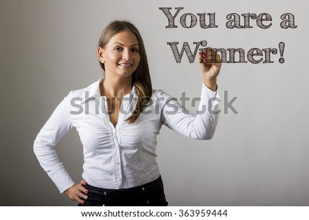 You are a Winner! - Beautiful girl writing on transparent surface - horizontal image