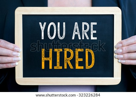 You are hired - Businesswoman holding chalkboard with text - Recruitment and human resources - stock photo