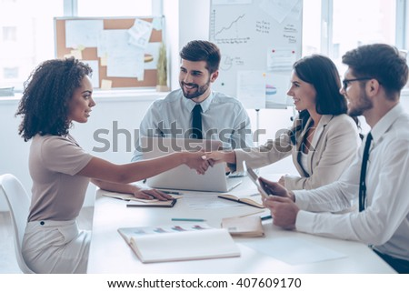 You are hired! Two beautiful women shaking hands with smile while sitting at the office table with their coworkers