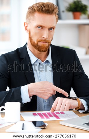 You are late! Confident bearded businessman looking at camera and pointing on his watch while sitting at his working place - stock photo