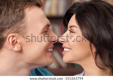 You are the love of my life. Beautiful young man and woman are flirting and smiling. They are touching their noses playfully - stock photo