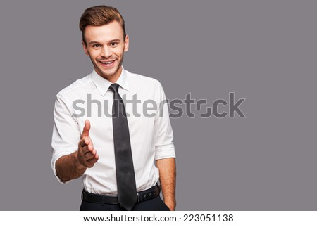 You are welcome in our company! Portrait of cheerful young man in formalwear stretching out hand for shaking while standing against grey background - stock photo