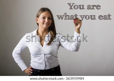 You are what you eat - Beautiful girl writing on transparent surface - horizontal image