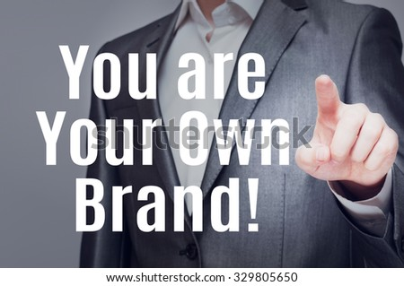 You Are Your Own Brand ! Businessman pointing to message text written on virtual screen - stock photo