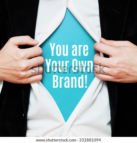 You Are Your Own Brand! Man showing a superhero suit underneath his shirt with a message text written on it. - stock photo