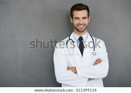 You can absolutely trust me. Confident young doctor in white uniform looking at camera and keeping arms crossed while standing against grey background - stock photo