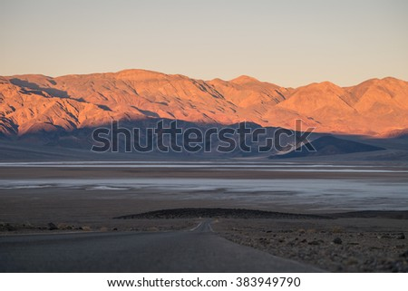 You can see the various landscape; salt flat, mountain ranges, and desert along the road. This one was taken on sunrise time. You can see the first light came across the mountain. - stock photo