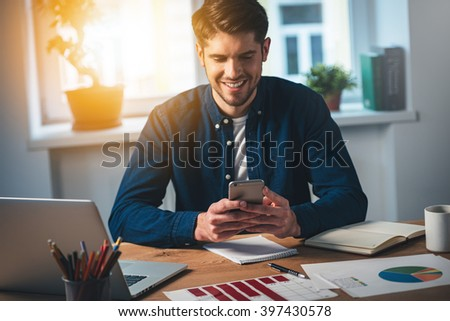 You have new message! Cheerful young handsome man using his smartphone with smile while sitting at his working place - stock photo