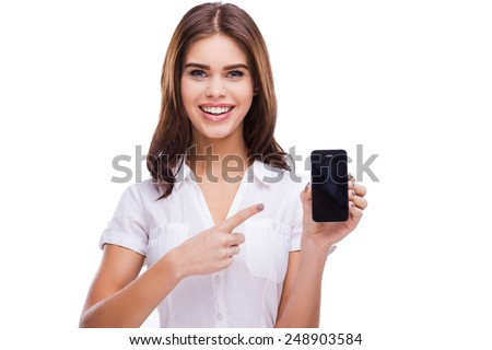 You may see you advertisement here. Beautiful young women holding mobile phone and pointing on it while standing against white background