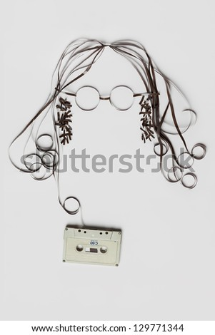 You need is tape. A beautiful image made of tape cassette with the tape forming a face of hair glasses on bright background. - stock photo