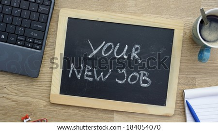 You new job written on a chalkboard at the office - stock photo