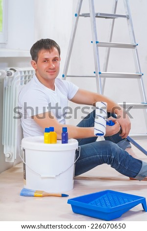 youg men sitting on the floor with painting tools and looking at camera - stock photo