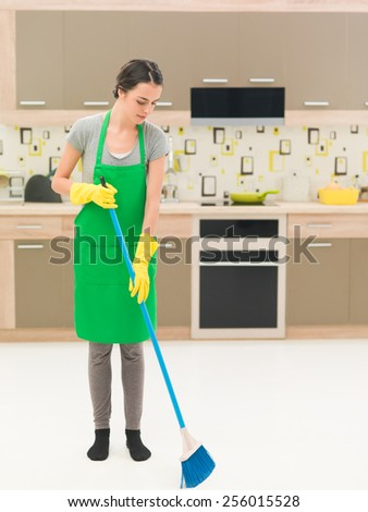 youn caucasian woman standing in kitchen, sweeping floor with broom - stock photo