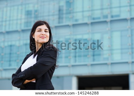 Youn entrepreneur cross her arms in front of a building - stock photo