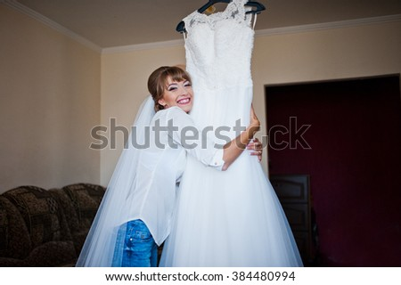 Youn happy bride looked at her wedding dress - stock photo