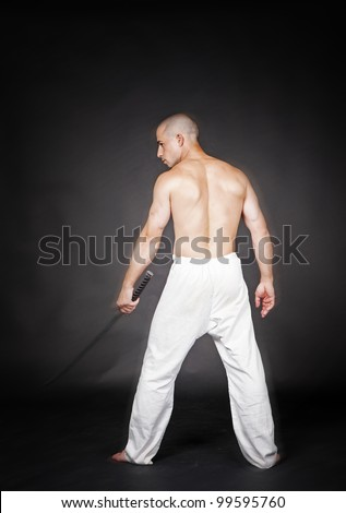 Youn man with japan sword in hands in studio - stock photo