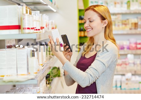 Youn woman comparing prices with her smartphone in drugstore department of a supermarket - stock photo