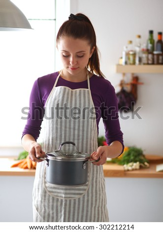 Youn woman holding pan in hands on kitchen - stock photo