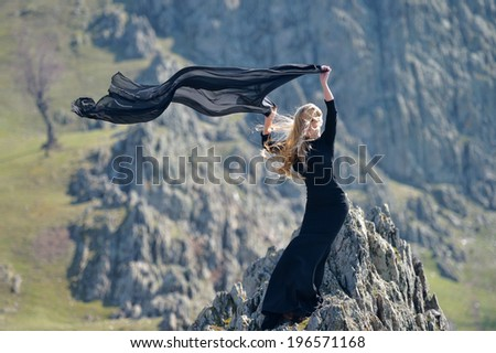 youn woman wearing black dress outdoor on rocks - stock photo