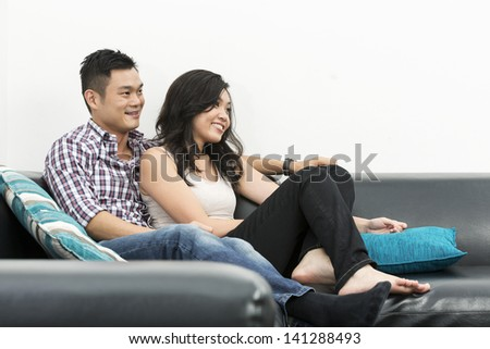 Yound and happy Chinese couple hanging out together at home