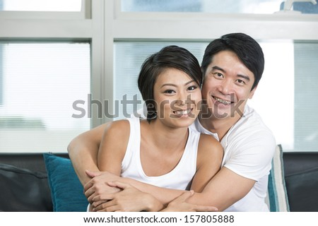 Yound and happy Chinese couple posing together at home - stock photo