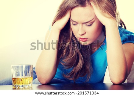 Yound beautiful woman in depression, drinking alcohol - stock photo