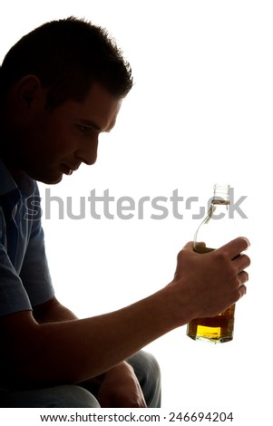 Yound man in depression, drinking whisky - stock photo