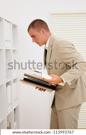 Young accountant collects folders in office