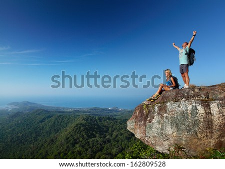 Young active couple enjoying view from top of a mountain - stock photo
