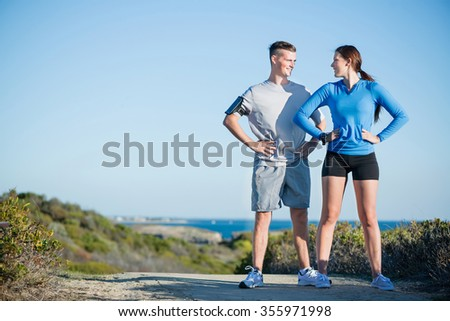 Young active couple of joggers on beach taking breath - stock photo