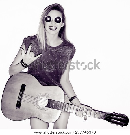 Young active dancing happy musician woman posing with guitar and round black sunglasses smiling and going crazy  - stock photo
