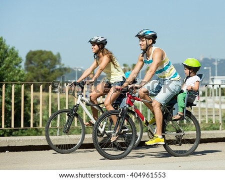 Young active family of four cycling on street road in summer day
