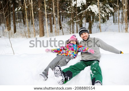 Young active father and his daughter having fun in deep snow on the bright winter day - stock photo