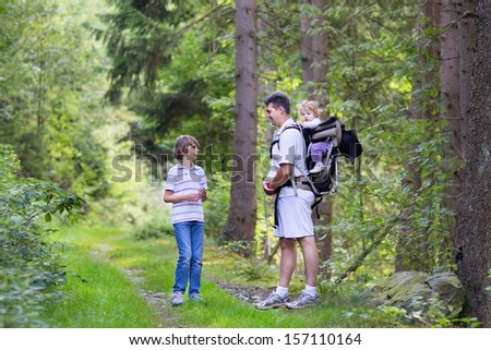 Young active father hiking with his school age son and baby daughter in a beautiful autumn forest - stock photo