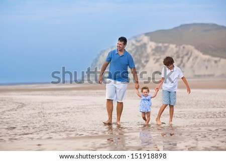 Young active father playing with his baby daughter and son on a beautiful beach - stock photo