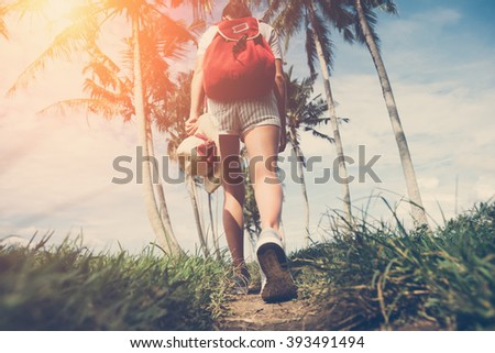Young active girl walking at sunny day near palm trees (intentional sun glare and vintage color)  - stock photo