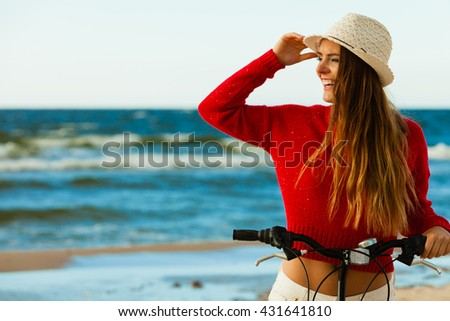 Young active girl with bicycle on seaside. Smiling cute woman resting near to sea in summer. Fashionable tourist on fresh air.