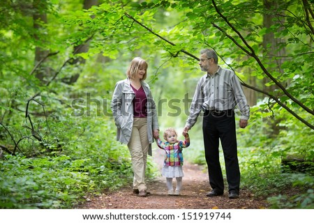 Young active grandparents hiking with their baby grand daughter in an autumn park - stock photo