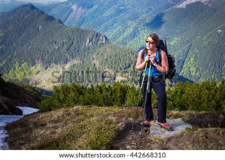Young, active hiker girl hiking alone in the carpathian mountains in Romania above valleys and forests in alpine condition at high altitude while enjoying her vacation. - stock photo