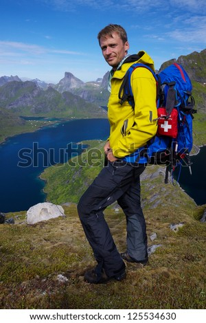 Young active man with backpack hiking on beautiful Lofoten islands in Norway on sunny day - stock photo
