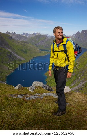 Young active man with backpack hiking on Lofoten islands in Norway on sunny day
