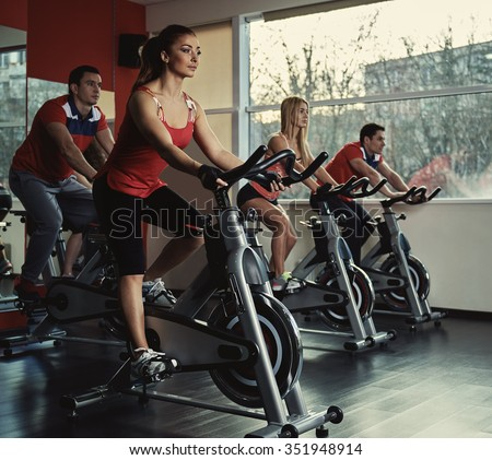 Young active people exercising in spinning class. Group of fit people doing sport in the gym. - stock photo