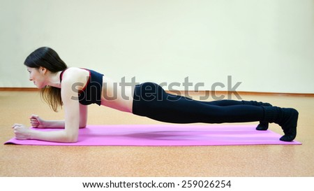 Young active woman doing plank exercise in a gym - stock photo