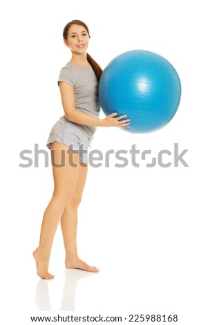 Young active woman holding fitness ball