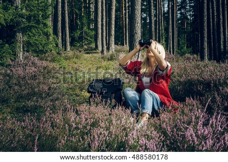 Young active woman tourist sits in a clearing in the woods and looking through binoculars. Healthy active lifestyle concept.