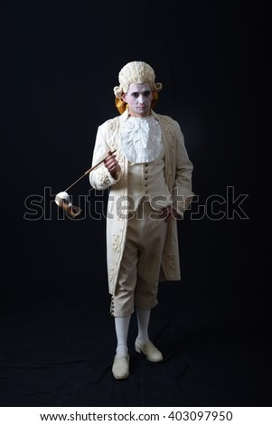young actor in a white wig holding a theatrical mask - stock photo