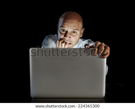 young addict man alone at night sitting at computer laptop - online gambling isolated on black background. - stock photo