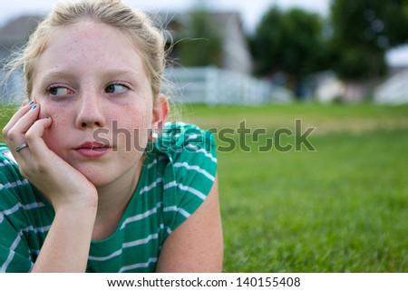 Young adolescent girl looking bored at a park. - stock photo
