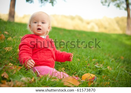 young adorable cheerful baby sit in park on green grass play with leaves